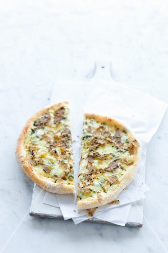 A pizza topped with creme fraiche, fontina cheese and truffles