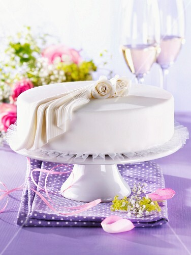 A white festive cake decorated with roses and fondant icing