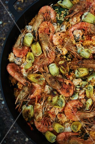 Shrimp Paella Cooking Over and Outside Open Fire