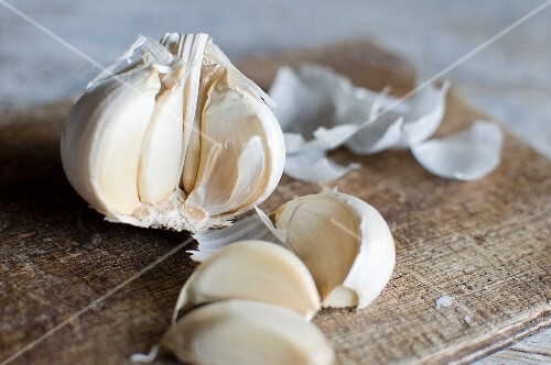 A split open garlic bulb on a wooden board