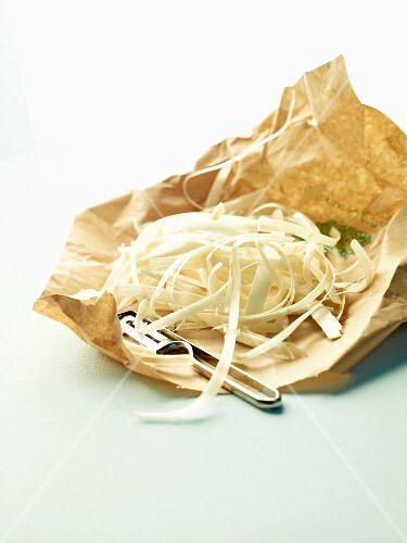 Asparagus peel on a paper with a peeler