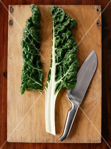 A chard leaf and a knife on a chopping board