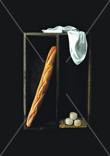 A baguette and goat's cheese in a wooden crate