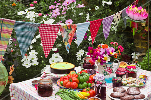 A table laid in a garden with biscuits, fresh vegetables, jam and cake