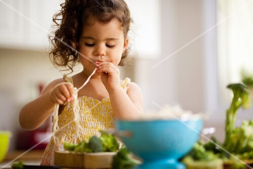 Girl (4-7) eating strand of spaghetti, side view