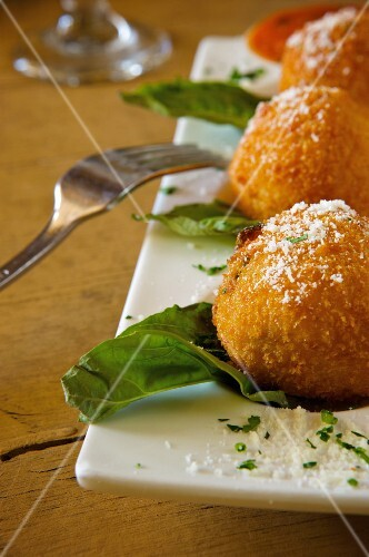 Deep Fried Risotto Balls on a Platter with Parmesan Cheese