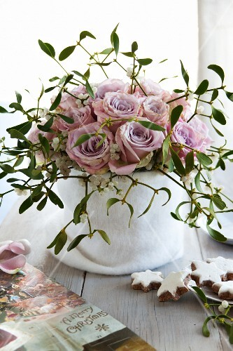A bouquet if pink roses and mistletoe