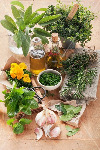 An arrangement of fresh herbs, garlic and oil