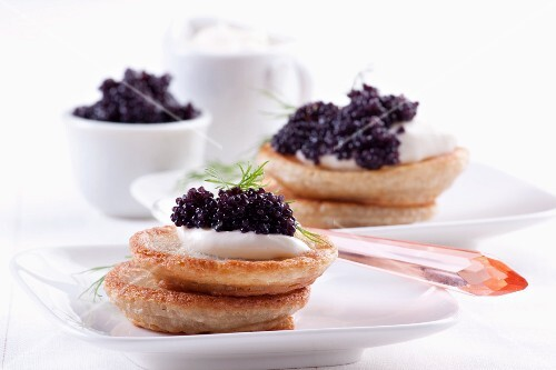 Blinis topped with sour cream and caviar