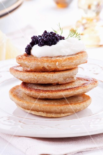 A stack of blinis topped with sour cream and caviar