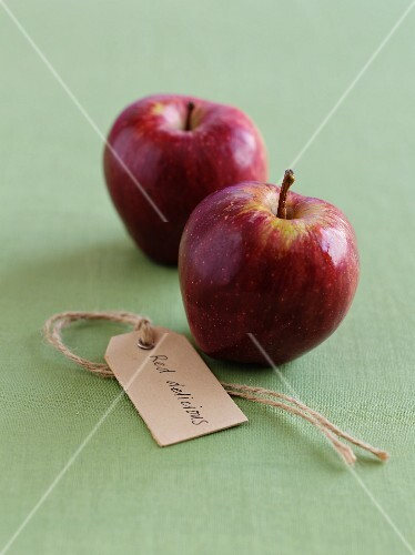 Two Red Delicious apples with a label