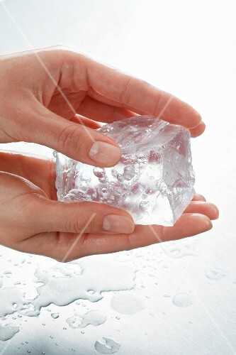 Hands holding a piece of ice