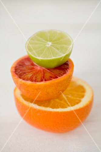 Half an orange, a blood orange and a lime stacked on top of each other