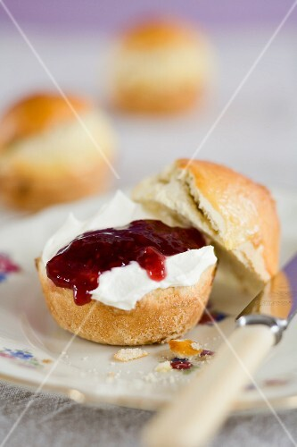 A scone spread with cream cheese and strawberry jam