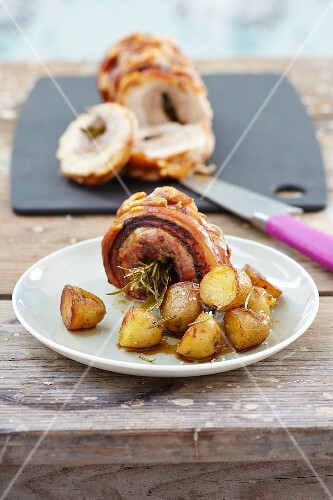 Stuffed roast pork roll with herbs and roast potatoes