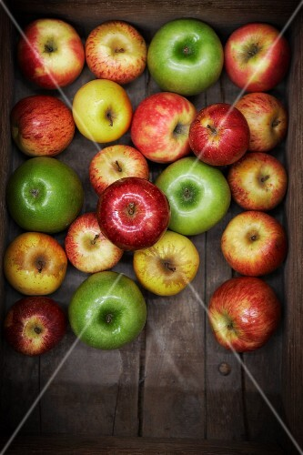 Assorted apples in a wooden crate (top view)