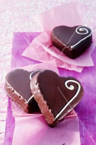 Three heart-shaped chocolates on purple paper
