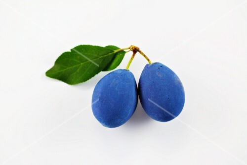 Two damsons on a white surface