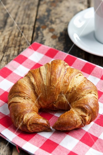 A croissant on a checked cloth