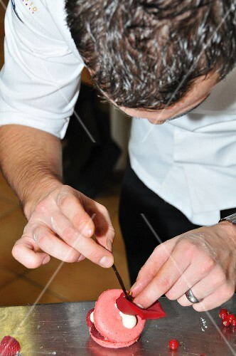 A chef decorating a raspberry tart with a rose petal
