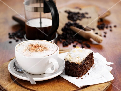 Coffee with foam and a piece of cake