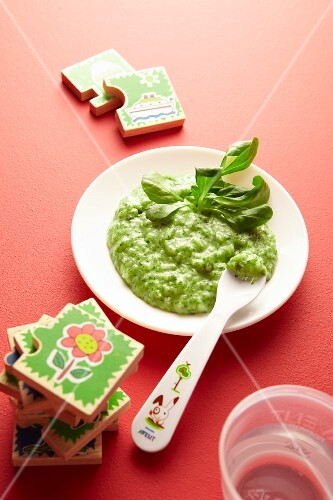 Baby food with green vegetables on a plate next to toys