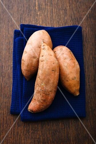 Three sweet potatoes on a tea towel