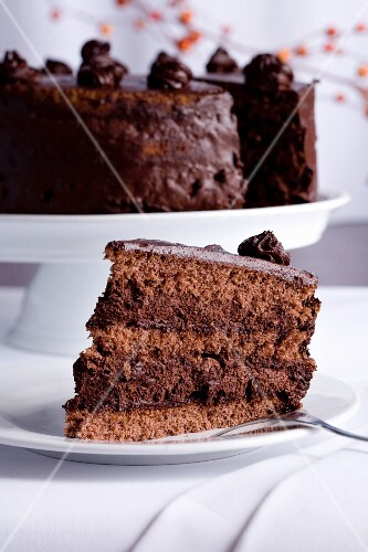 A slice of chocolate cake with the rest of the cake in the background