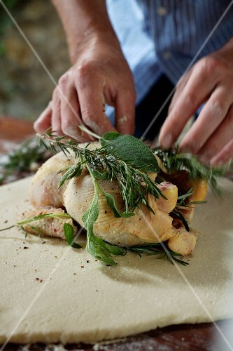 Stuffing a chicken with herbs