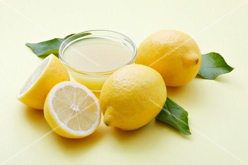 A bowl of lemon juice and fresh lemons
