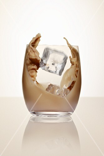 An ice cube falling into a glass of cream liqueur