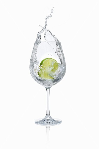 A lime slice falling into a glass of water