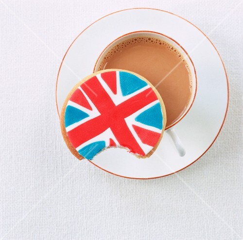 A Union Jack biscuit with a bite taken out balanced on a cup of tea