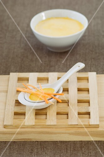 Carrot soup with carrot strips on an Oriental spoon