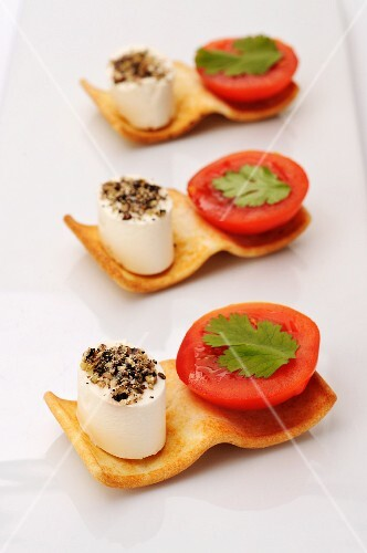 Canapes with cream cheese, tomatoes and coriander