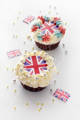 Two cupcakes topped with cream and Union Jacks