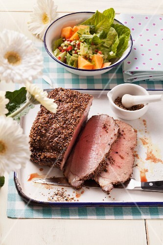 Roast beef with a pepper crust and a melon salad