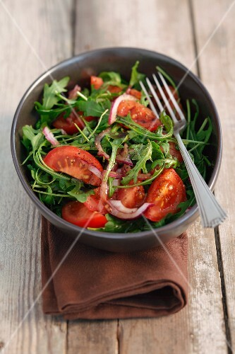 Rocket salad with cherry tomatoes, onions and balsamic vinegar