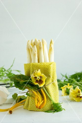 Peeled white asparagus wrapped in a tea towel