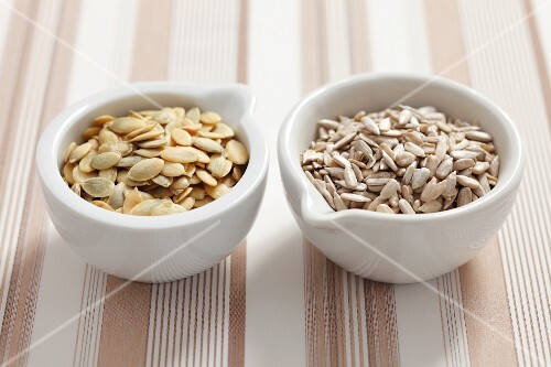 Pumpkin seeds and sunflower seeds in bowls