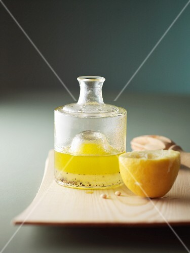 Salad dressing made with oil, lemon juice and pepper in a glass bottle
