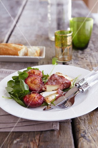 Brie wrapped in bacon with roasted plums and pesto sauce