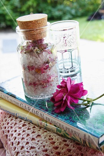 Scatter cushion with crocheted cover, books, rose bath salts, drinking glass and rose
