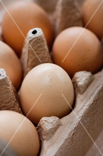 Brown eggs in an egg box (close-up)