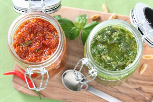 Spicy red pesto and basil pesto in jars
