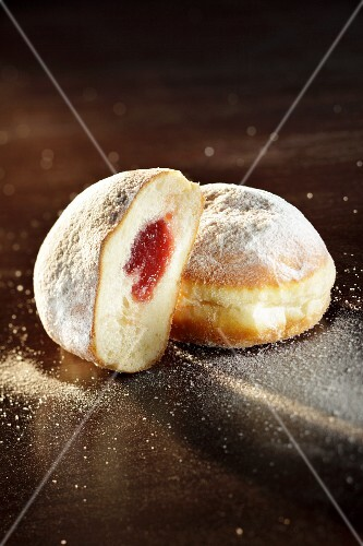 Doughnuts, whole and halved, dusted with icing sugar