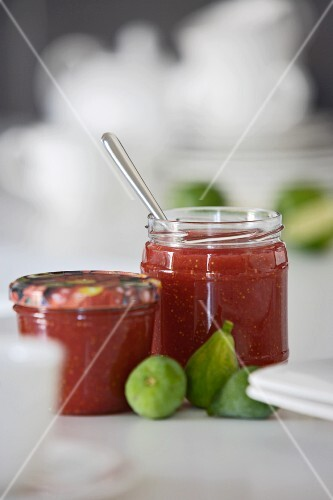 Two jars of strawberry jam and fresh figs