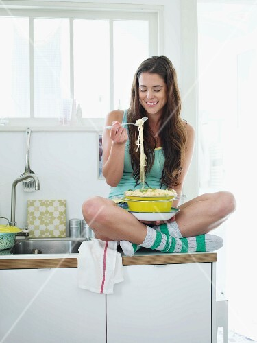 A young woman sitting cross-legged on a work surface eating spaghetti