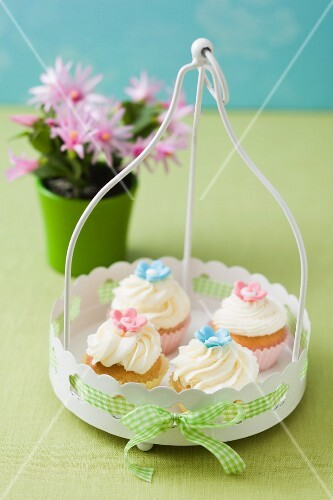 Four cupcakes decorated with pink and light-blue sugar flowers