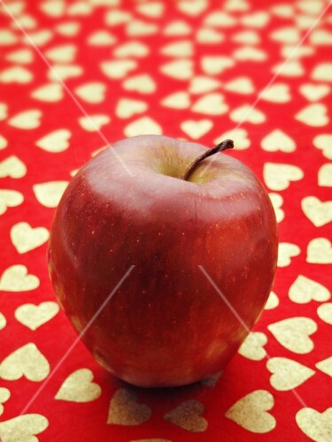A red apple on a red surface patterned with hearts